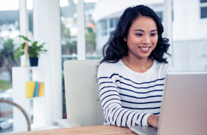 A smiling asian women with a striped shirt typing on her laptop in an office