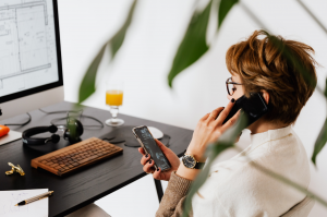 Woman on talking on phone while sitting in front of the computer.
